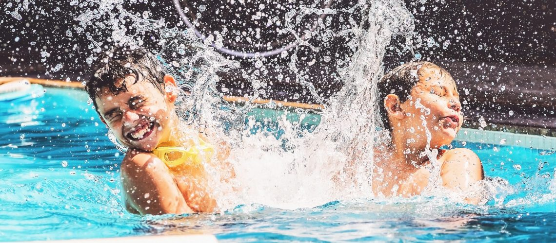 Two boys at the swimming pool splashing water and having fun. Friends playing on the water of a summer day.